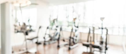 Out of focus shot of a gym with exercise bikes in it