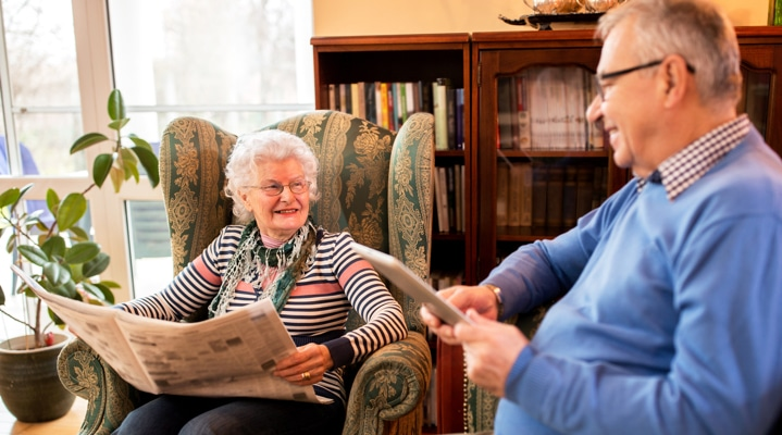 two residents smiling while reading
