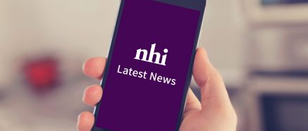 Hand holding mobile phone with Nursing Homes Ireland news on it