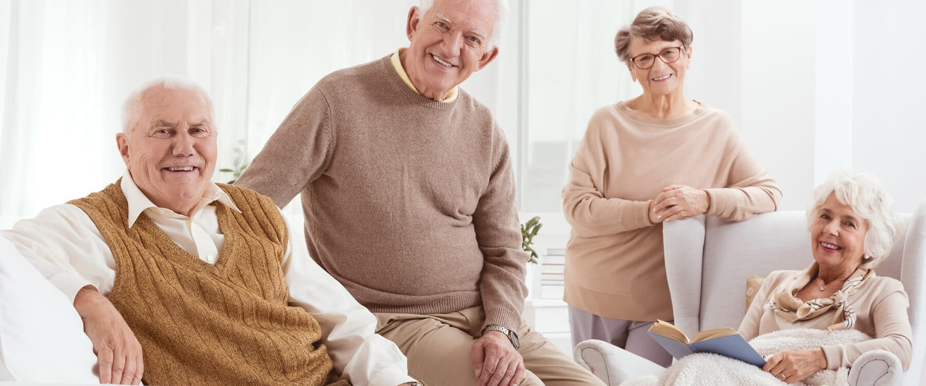 four older people smiling enthusiastically